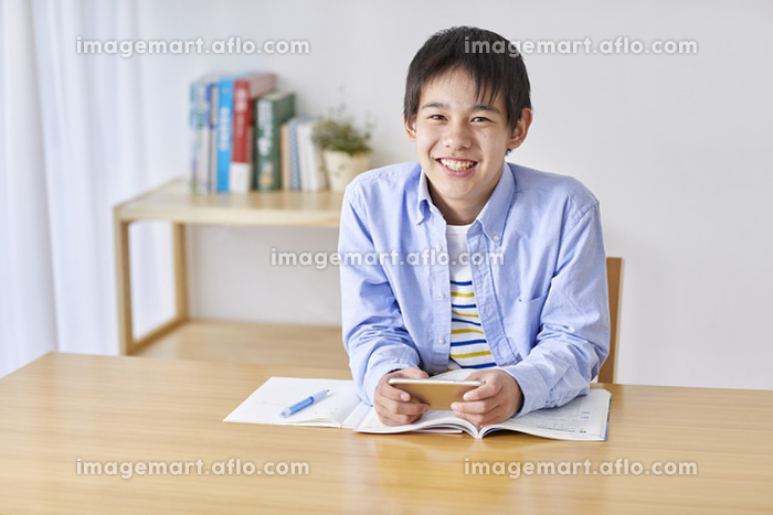 スマートフォンを見て勉強する男子中学生の販売画像