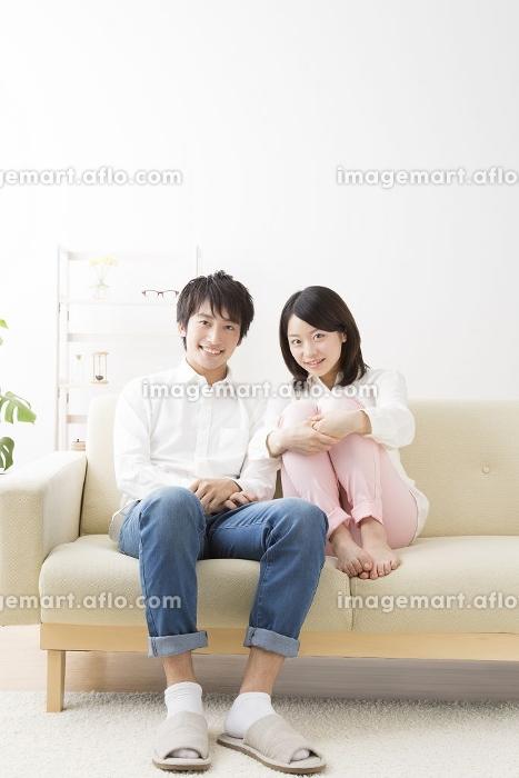 ソファーに座って微笑むカップル