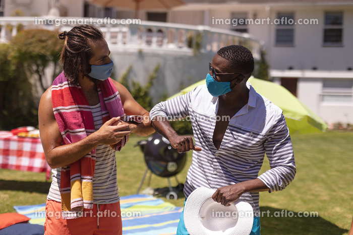 Two diverse male friends wearing face masks bumping elbows at a pool party. Health and hygiene precautions while hanging out and relaxing outdoors in summer during coronavirus covid 19 pandemic.の販売画像