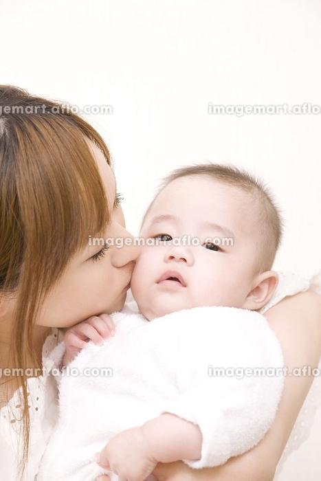 母親にキスをされる赤ちゃんの販売画像