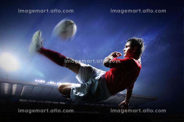 ボレーキックをするサッカー選手