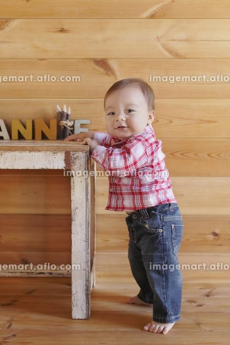 つかまり立ちする赤ちゃんの販売画像