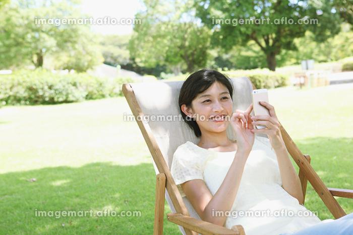 デッキチェアでくつろぐ日本人女性の販売画像