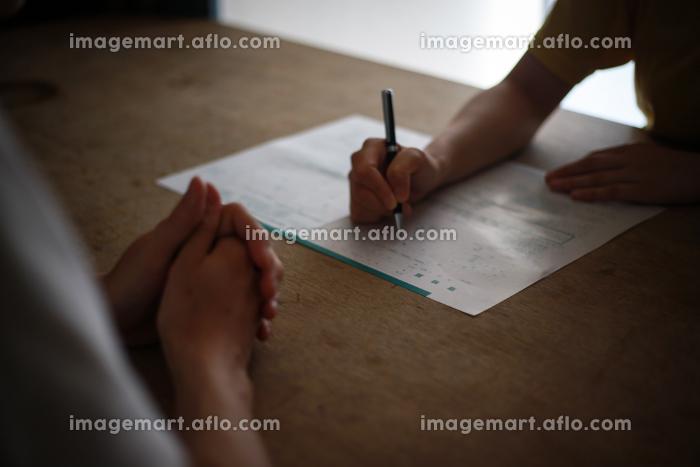 離婚届に記入する夫婦の販売画像