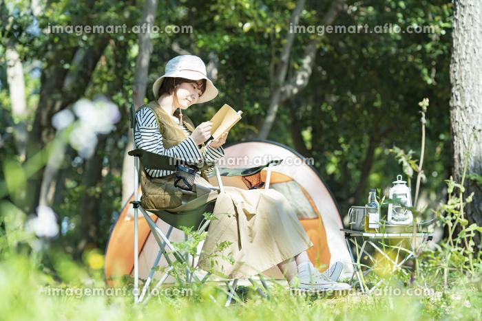 ソロキャンプイメージ・本を読む若い女性の販売画像