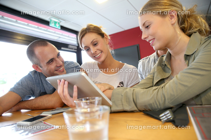 Group of friends in campus lounge websurfing with tabletの販売画像