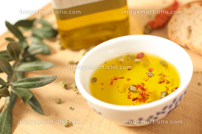 Close up view of  olive oil  in porcelain bowl with thyme and olive twig over wooden table  with a shallow depth of focusの販売画像