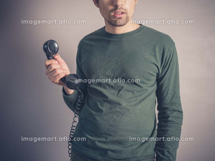A concerned and worried looking young man is holding the receiver of a vintage rotary phoneの販売画像