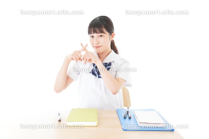 バツを示す制服姿の女子学生の販売画像