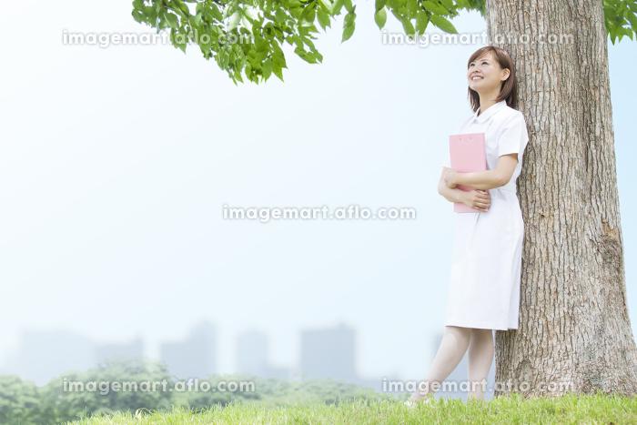 木にもたれる看護師さん