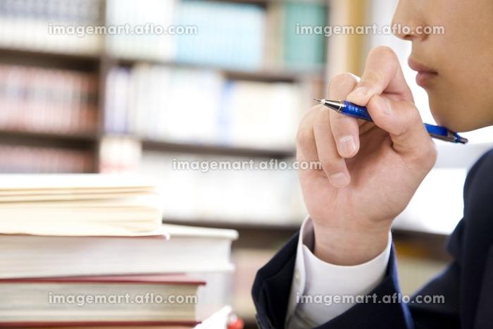 図書室で勉強する男子中学生