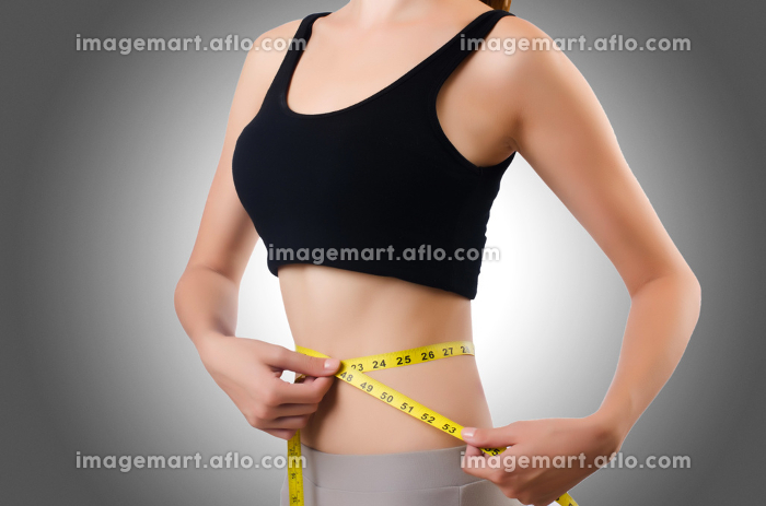 Young girl with centimeter in dieting conceptの販売画像