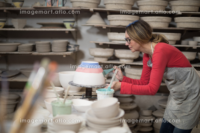 Female potter painting bowlの販売画像