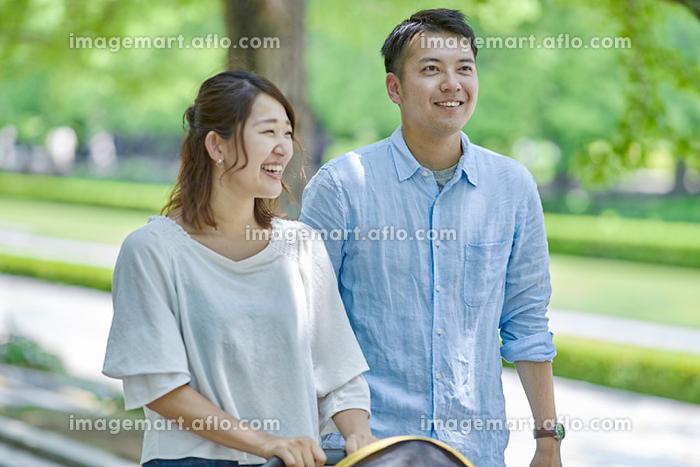 新緑の並木道を散歩する家族の販売画像
