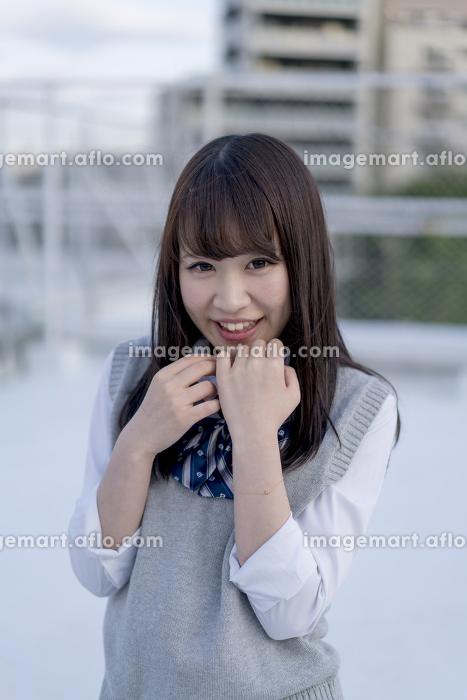 学校の屋上で胸に手をあてる女子高生の販売画像