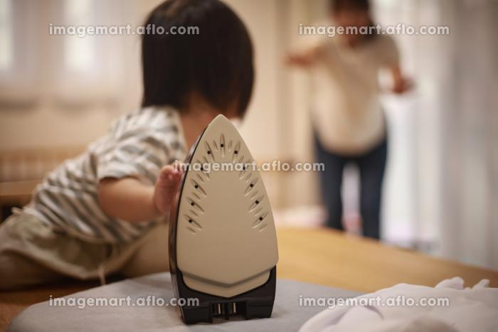 アイロンに触れようとする女の子の販売画像