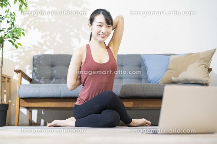 パソコンの画面を見ながらヨガをする女性の販売画像