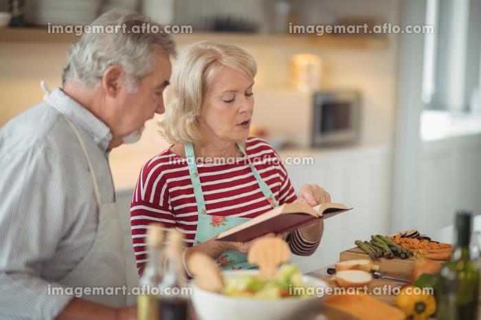 Senior couple reading recipe book while preparing mealの販売画像
