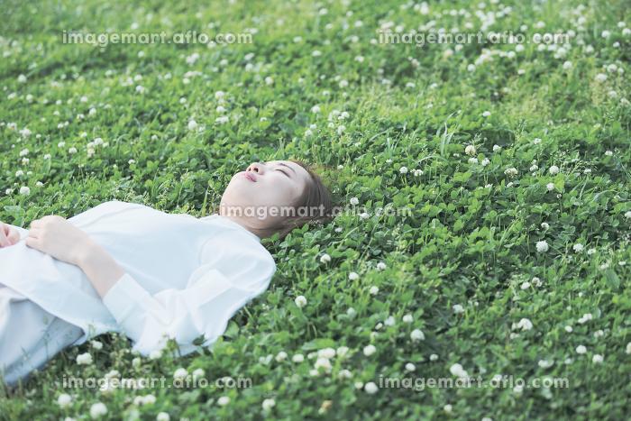 芝生でくつろぐ女性の販売画像
