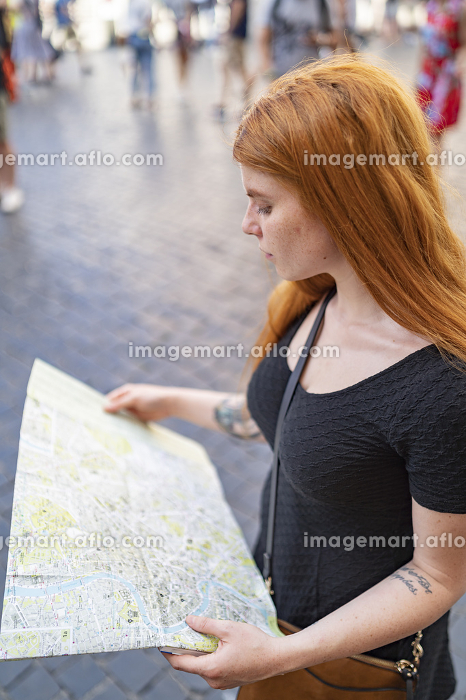 Red hair woman reading a city map in the city background