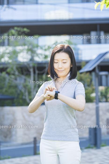 屋外でスマートウォッチを操作する中年女性の販売画像