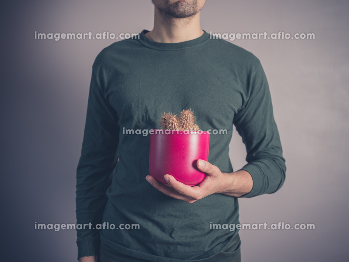 A young man wearing a green top is holding a cactusの販売画像