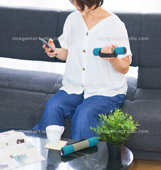 自宅リビングで配信動画を見つつダンベル運動をする中年女性【ニューノーマルのライフスタイル】の販売画像