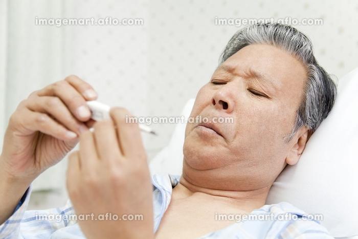 体温計を見つめる患者