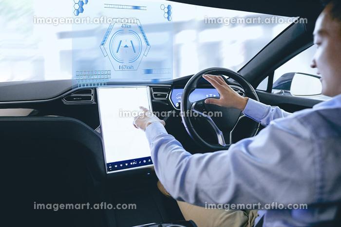 自動運転車を運転する日本人男性の販売画像