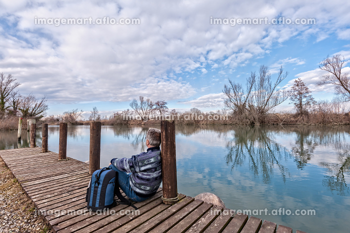 Hiker with backpack over wood pier on shore of river.の販売画像