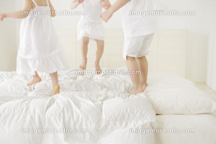 ベッドの上で飛び跳ねる女の子と男の子の足の販売画像
