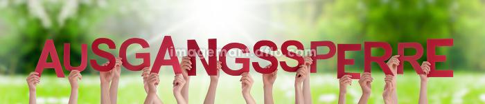 People Hands Holding Word Ausgangssperre Means Curfew, Grass Meadowの販売画像