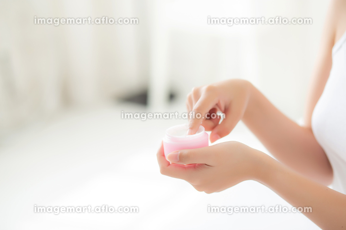 Beautiful with closeup hand asian woman applying moisturizer or