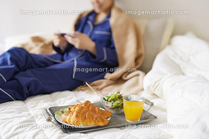 ベッドルームで朝食をとる女性