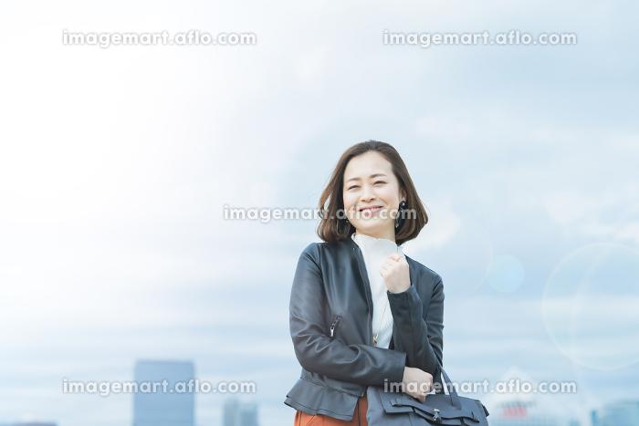 笑顔で通勤するカジュアルな服装のビジネスウーマンの販売画像