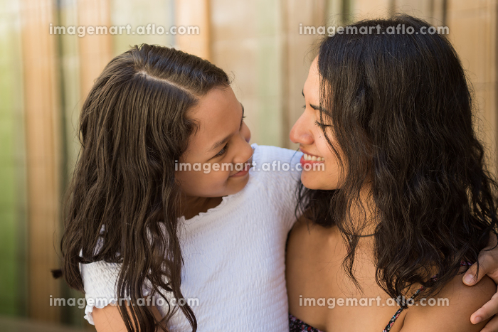Young beautiful latin mother and daughter looking at each other and smiling.の販売画像