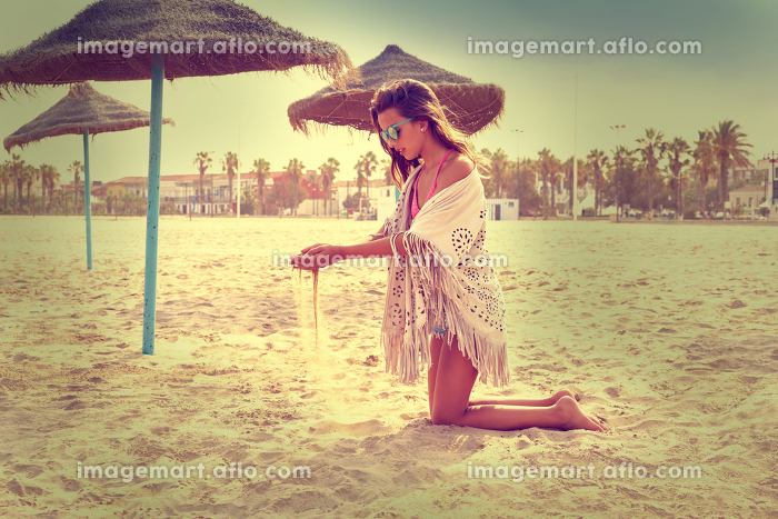 Teen girl on the beach playing with sand near thatch umbrellas filtered imageの販売画像