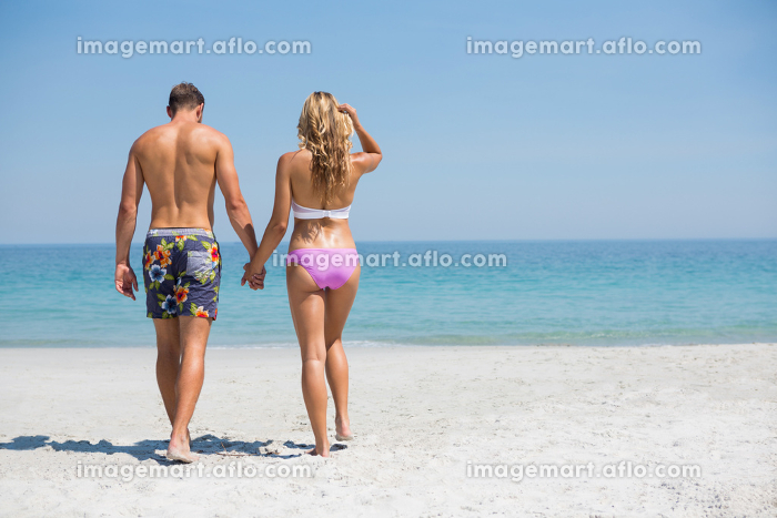 Rear view of couple walking at beachの販売画像