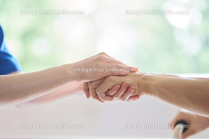 介護士と高齢者の手元の販売画像