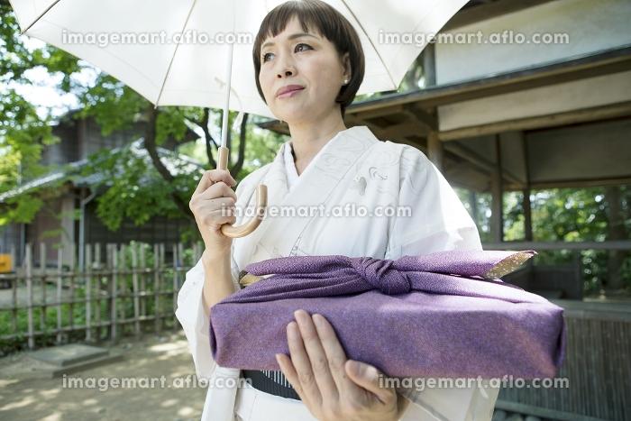 風呂敷包みを持つ着物の日本人のシニア女性の販売画像