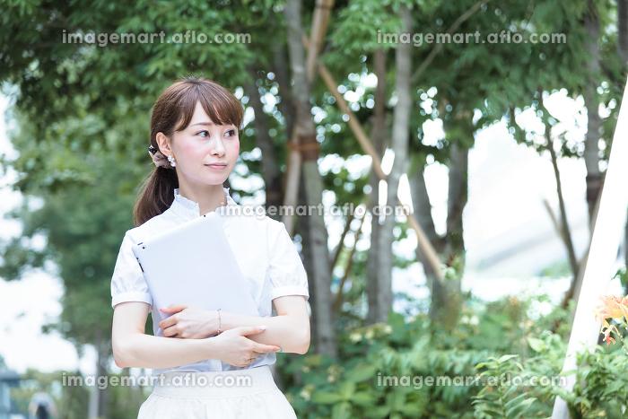 屋外でタブレットPCを持つ若い女性の販売画像