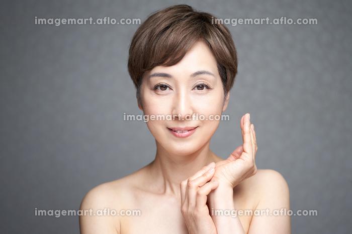カメラ目線でポーズをとる中年の日本人女性の販売画像