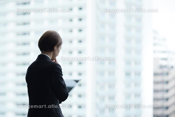 タブレットPCを使用する女性・都市風景バックの販売画像