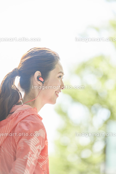 音楽を聴くランニングウェアの日本人女性の販売画像