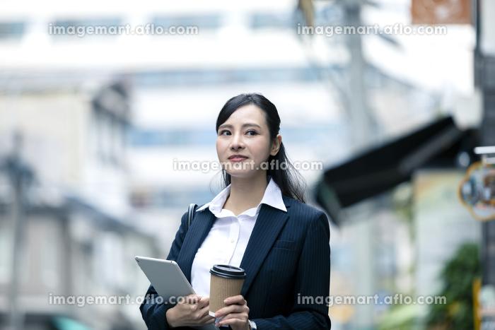 タブレットPCとドリンクを持つビジネスウーマン