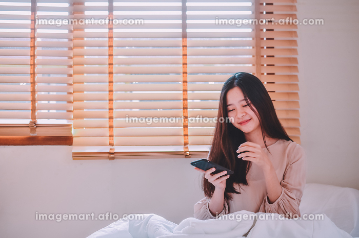 Women holding Mobile smartphone sitting on bed in roomの販売画像