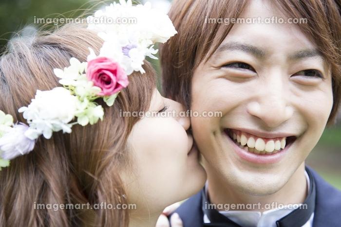 新郎の頬にキスをする新婦の販売画像