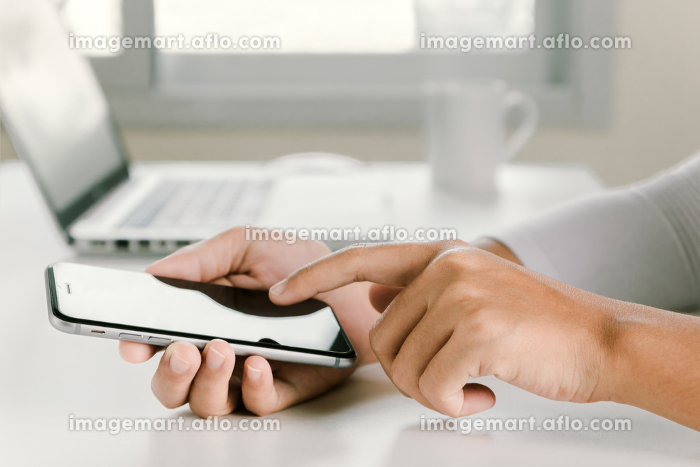 closeup woman hand using phone on workspace in officeの販売画像