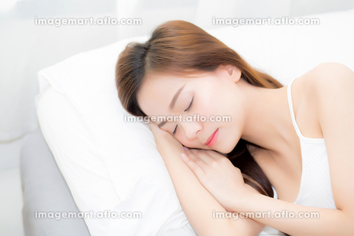 Beautiful asian young woman sleeping lying in bed with head on p