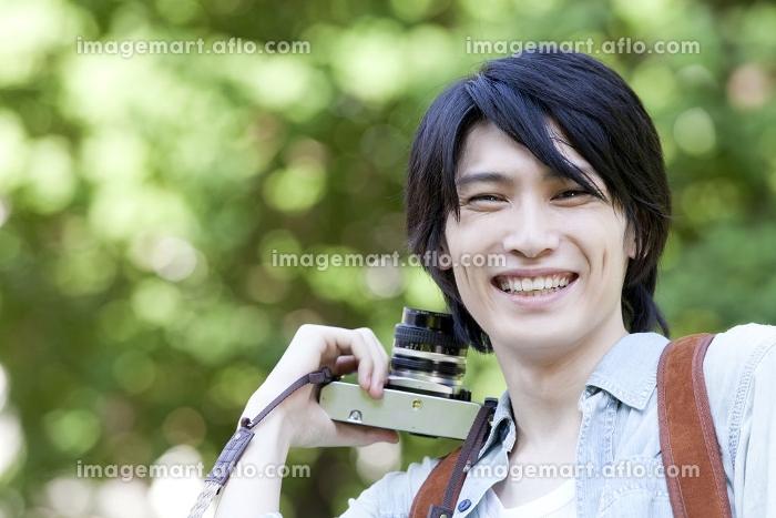 カメラを持って微笑む男子大学生の販売画像